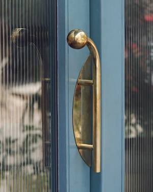 Site Practice - Brass door handle and other bespoke details contrast with the cool tones of blue. Photo: Americano
